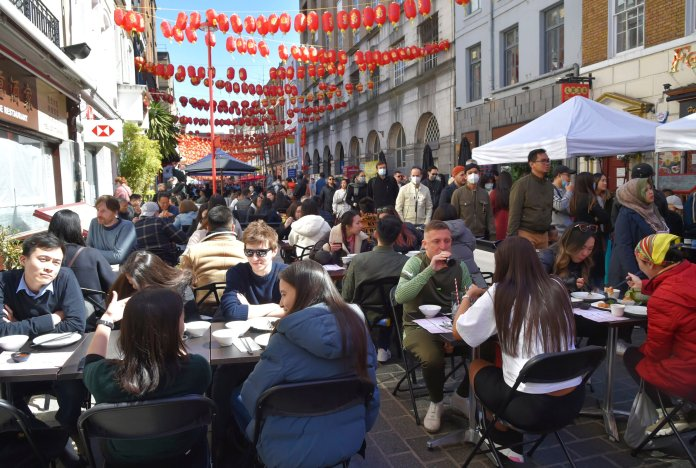 People enjoying outdoor restaurants in Chinatown, London.  The British rushed to take advantage of the first weekend since the pubs opened in sunny spring.