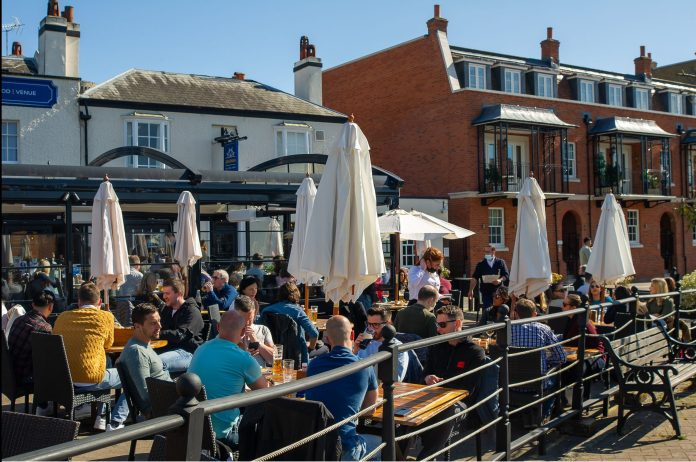 People seated at outdoor tables at the Boatman pub in Windsor.  The British rushed to take advantage of the first weekend since the pubs opened in sunny spring.