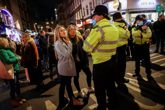 Police officers talk to drinkers in Soho.  The British rushed to take advantage of the first weekend since the pubs opened under the spring sun.