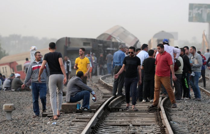 epa09143787 People stand near the damaged cars of a derailed passenger train in Toukh, Al Qalyubia Governorate, north of Cairo, Egypt on April 18, 2021. According to the Ministry of Health, 97 people were injured when several cars of a passenger train heading for the city of Mansoura derailed.  EPA / KHALED ELFIQI