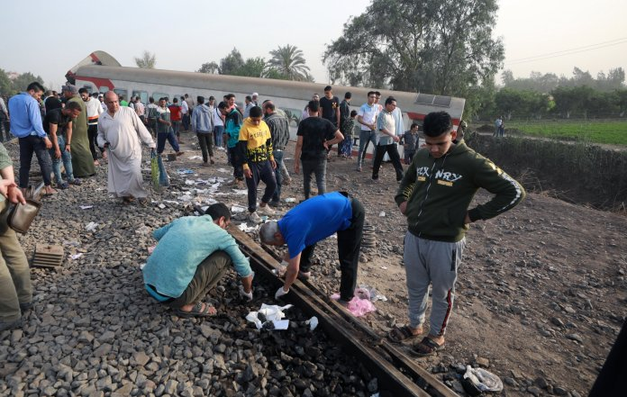 epa09143862 People stand near the damaged cars of a derailed passenger train in Toukh, Al Qalyubia governorate, north of Cairo, Egypt on April 18, 2021. According to the Ministry of Health, 97 people were injured when several cars of a passenger train heading for the city of Mansoura derailed.  EPA / KHALED ELFIQI
