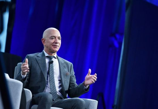 Ex-Amazon CEO Jeff Bezos sitting in a chair on a stage giving a talk to an audience.