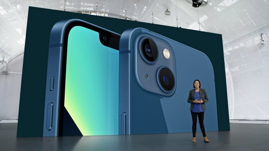 Apple's Kaiann Drance stands in front of an image of the iPhone 13