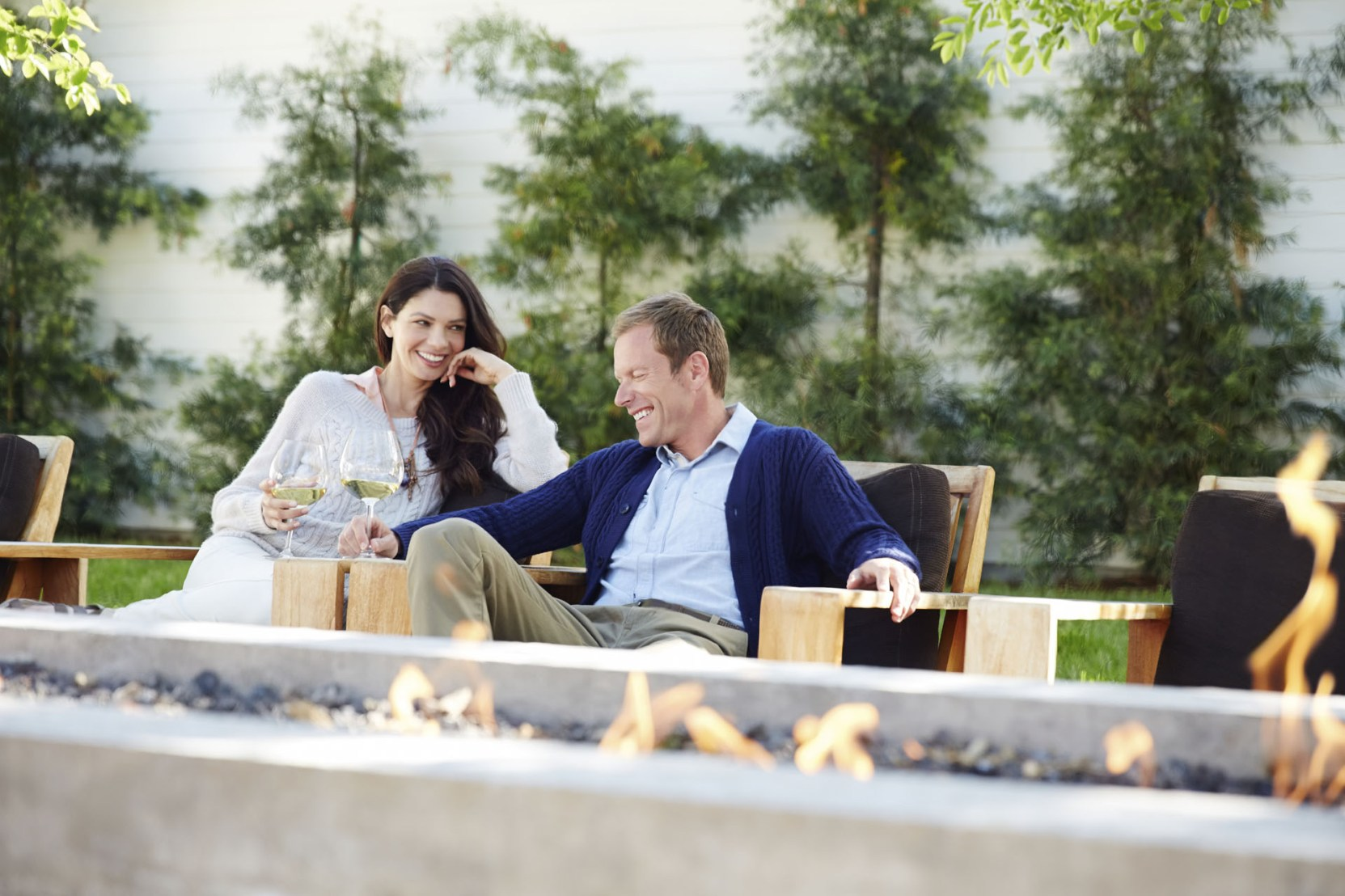 Couple With Wineglasses Sitting On Chairs At Outdoor Restaurant