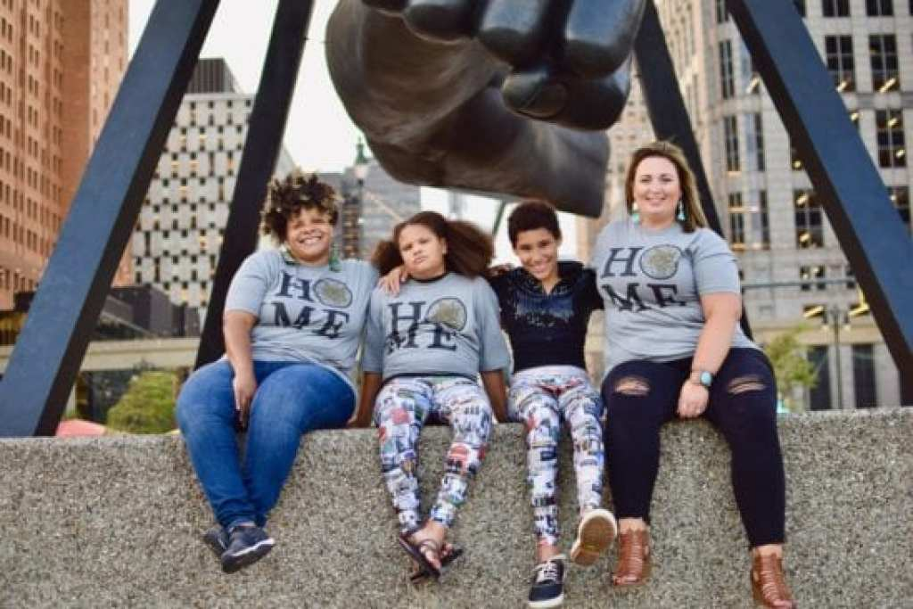 Liv, Clara, AJ and Carissa wearing Detroit Has Legs T-shirts and leggings in front of the Monument to Joe Louis, Hart Plaza Detroit