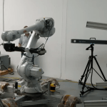 Real-Time Photogrammetry Guides Submillimetre Robot Positioning