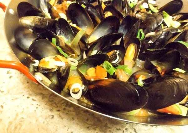 Mexican Mussels In White Wine cooked and served in a paella pan.