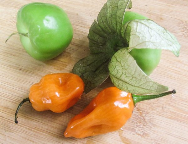 Tomatillos and habanero peppers on a wooden cutting board for the Habanero Tomatillo Salsa