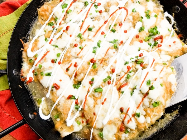 For a delicious comfort meal or appetizer, you will not want to miss out on these Creamy Cheesy Beef Enchiladas in Green Sauce. Made with corn or flour tortillas, perfectly seasoned ground beef, black beans and smothered in a delicious green sauce/salsa verde. Then topped with scallions, queso fresco and mexican crema or sour cream. Cooked and served in a paella pan. Yummy!