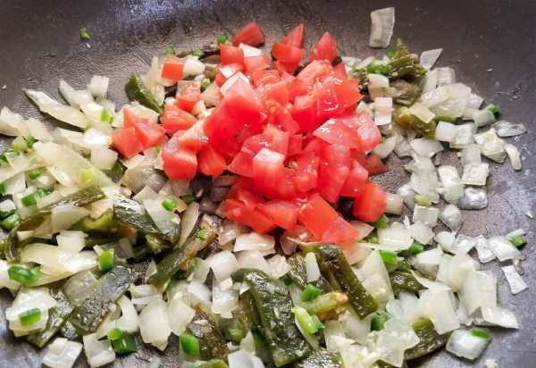 Onions, peppers, jalapeno, garlic and tomatoes cooking for authentic migas recipe.