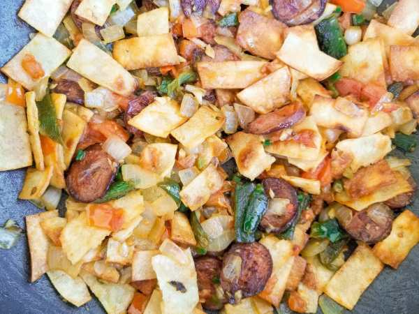 Mixture of onions, peppers, tomatoes, jalapeno, garlic, kielbasa sausage and tortilla strips for authentic migas recipe.