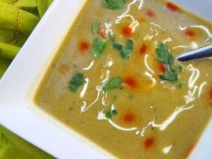 Roasted Poblano Soup served in a white bowl and topped with crema, hot sauce and chopped fresh cilantro.