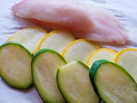 Preparing tilapia fillets with zucchini and yellow squash on top of parchment paper-Tilapia en Papillote Packets (Tilapia in Parchment Packets).
