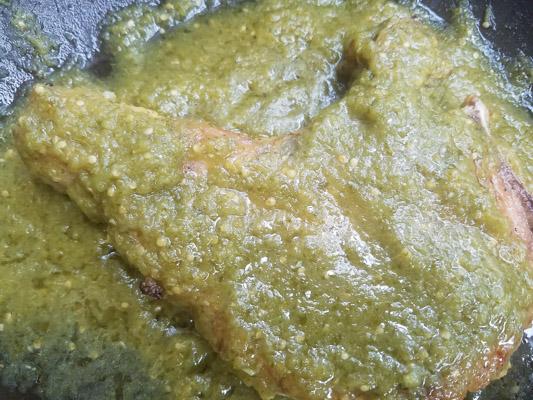 Chuletas de Puerco or Chuletas de Puerco en Salsa Verde (Pork Chops in Salsa Verde) cooking in a skillet.