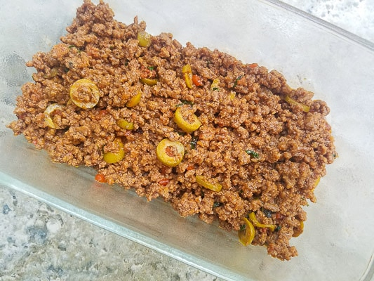Preparing the pastelón-A layer of picadillo (ground beef) on top of the plantains in a meatloaf pan.