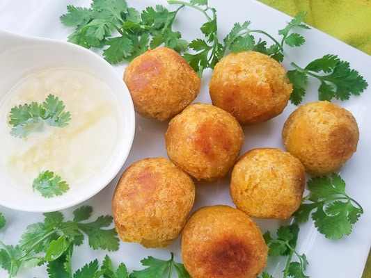 Bolón de Verde served on a bed of fresh cilantro on a white platter with a side of garlic aioli.