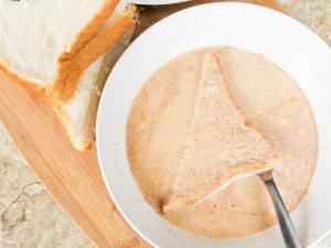 Soaking the bread slices in egg dulce de leche mix.