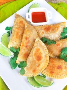 Empanadillas de Carne (Puerto Rican Empanadas) on a white platter with a side of hot sauce.