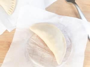 Forming the half moon shape for the empanadillas de carne (Puerto Rican empanadas)