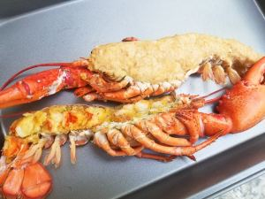 Stuffed whole lobster halves on a wooden cutting board.