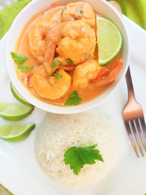 Camarones a la Crema served with white rice and limes on a white platter.
