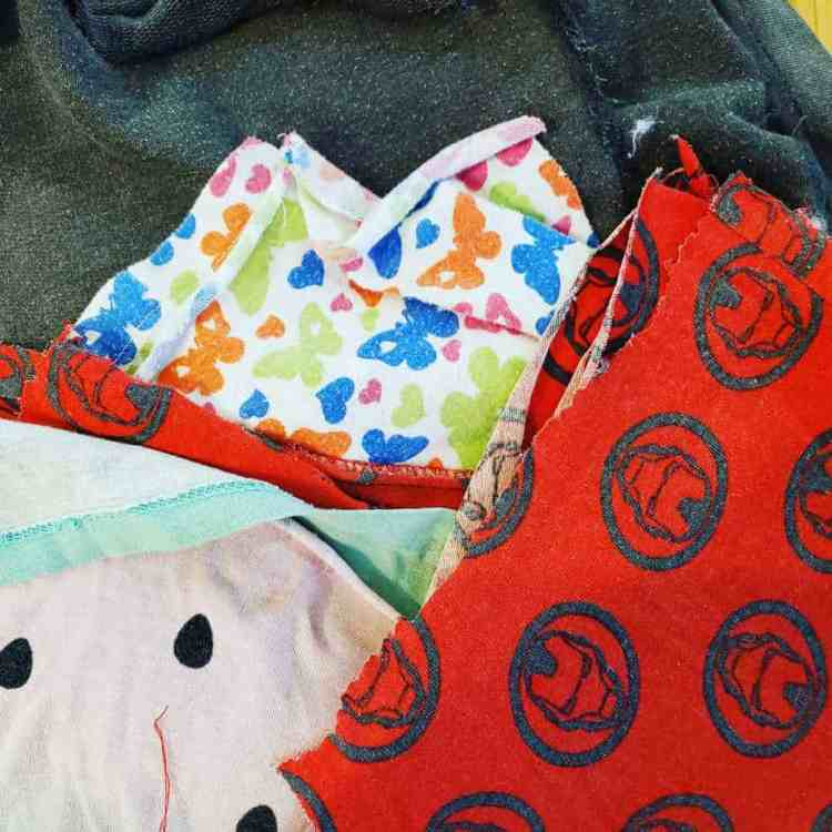 pile of old clothes cut up for napkins red with ironman image, pink watermelon and butterfly pattern)