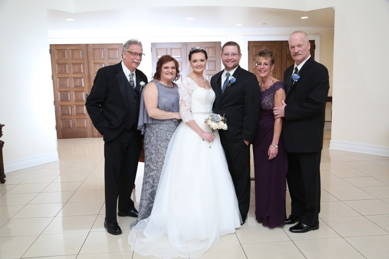 The bride and groom with their families at the caridge house