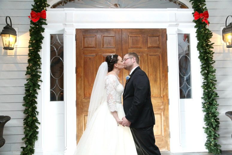 the bride and groom at the carriage house kissing