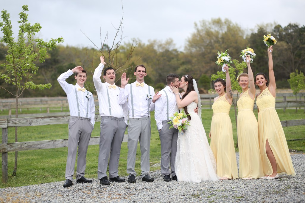 bride and groom kissing alongside bridesmaids and groomsmen
