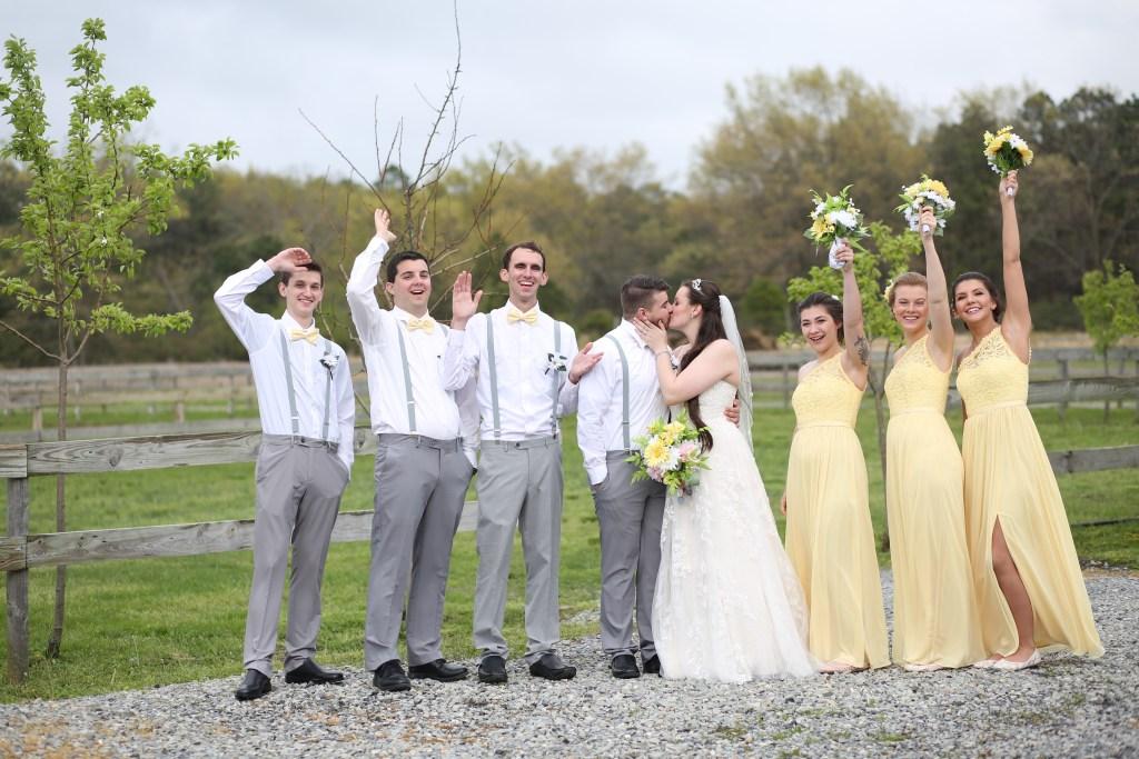 bride and groom kissing alongside bridesmaids and groomsmen