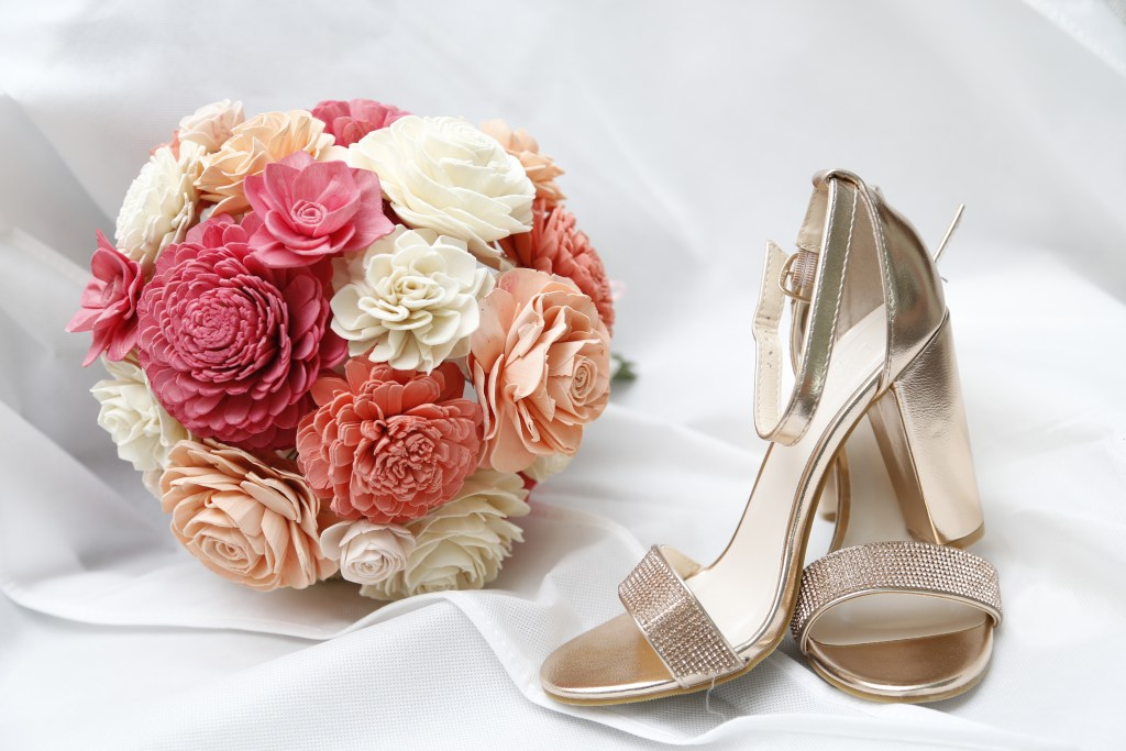bouquet and heels on top of white cloth at wedding in 2019