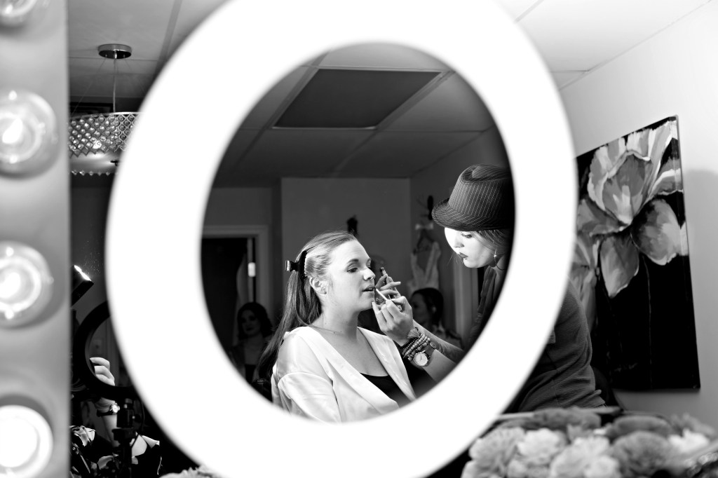 bride having makeup put on her by makeup artist at a wedding in 2019
