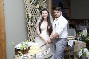bride and groom cutting wedding cake