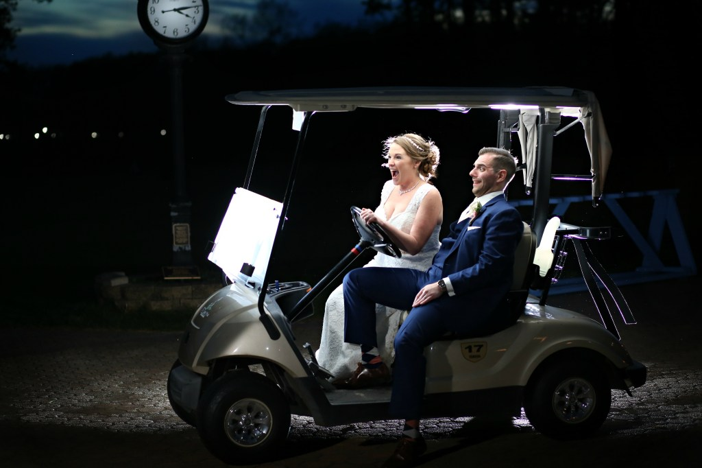 bride driving a golf cart at night in NJ with comically worried groom