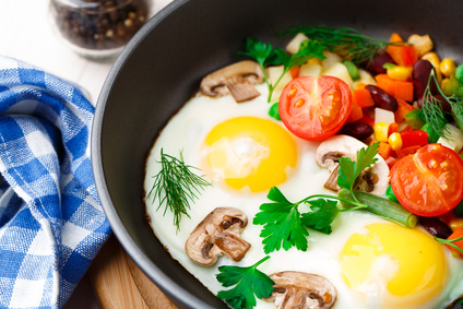 Fried eggs in a pan with vegetables