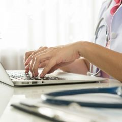 46989145 - close-up of a doctor typing on keybord in the office