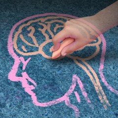 21492093 - children education concept  and school learning development with the hand of a child drawing a human head and brain with chalk on a cement floor as a symbol of mental health issues in youth