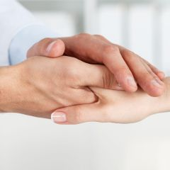 42889828 - friendly male doctor's hands holding female patient's hand for encouragement and empathy. partnership, trust and medical ethics concept. bad news lessening and support. patient cheering and support