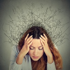 Stressed woman holding head in her hands