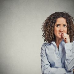 Closeup portrait nervous looking woman biting her fingernails craving something anxious isolated grey wall background with copy space. Negative human emotion facial expression body language perception