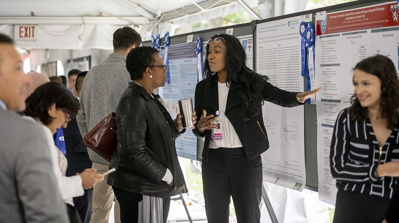 A researcher discusses her science during a poster session of clinical research day.