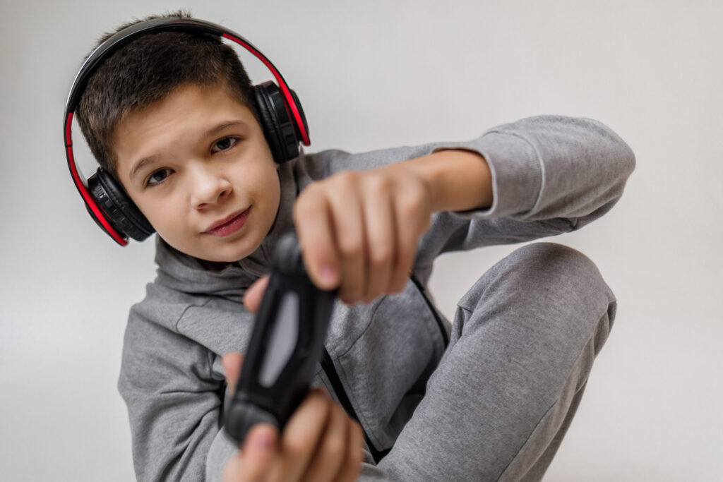 concentrated child boy playing video games over gray background. young gamer playing with game console