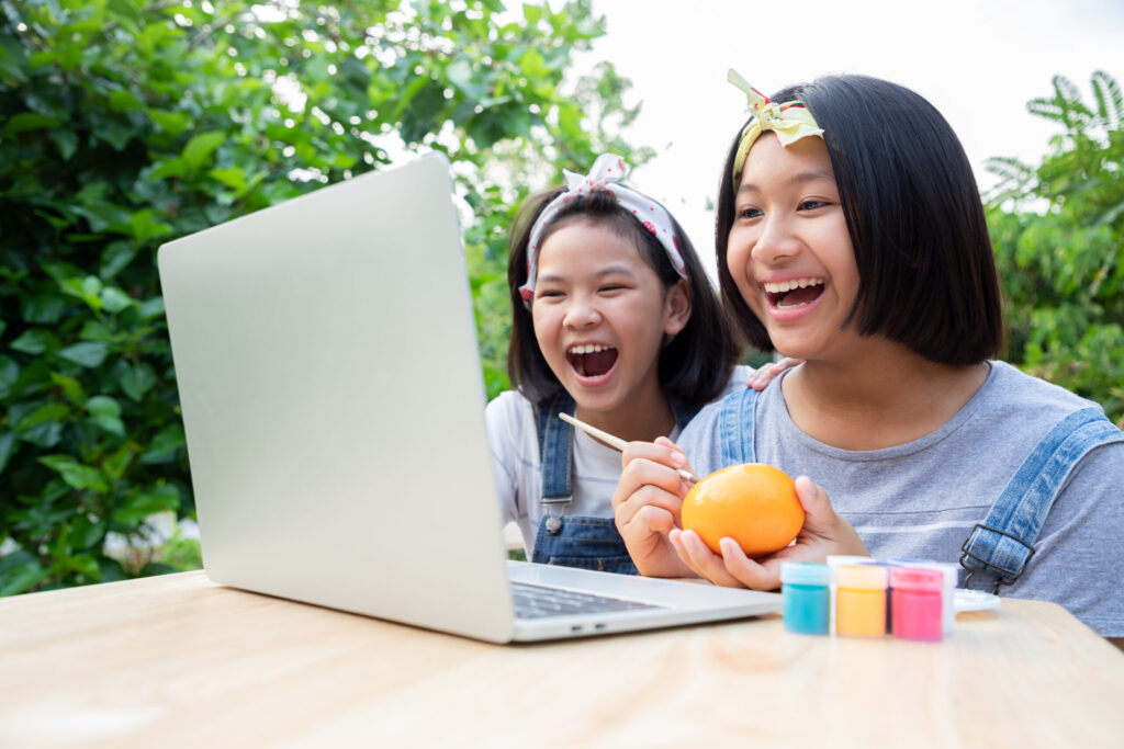 Two little girls are learning through online lessons in the front garden. They were smile and happiness to learn art subject. Protect corona virus new strain, or COVID-19. Education from home.
