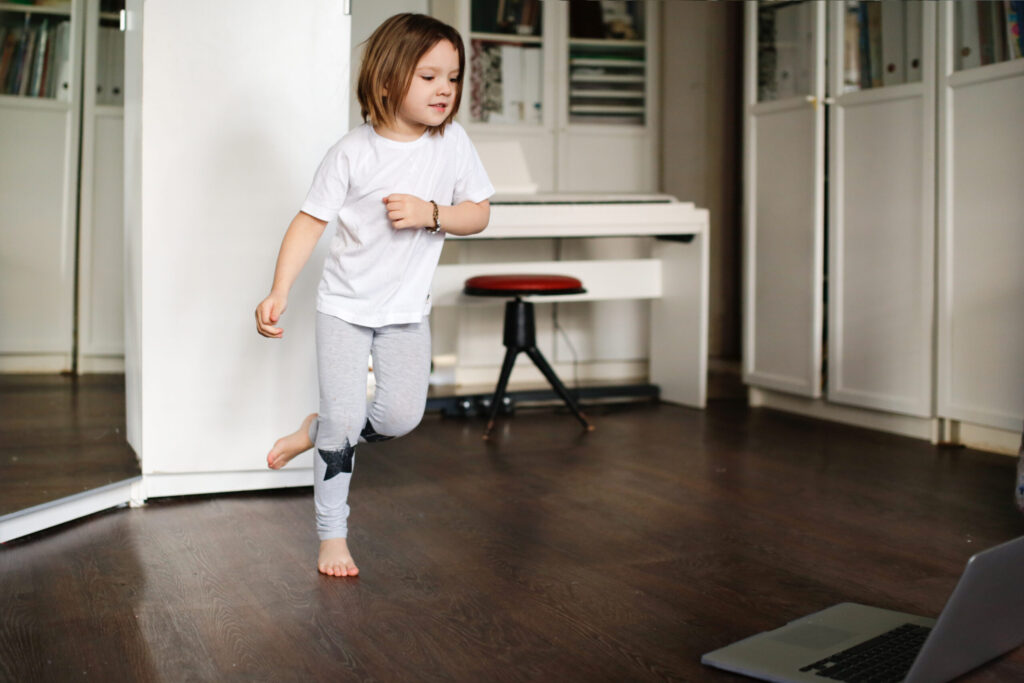 child girl is engaged in dancing, aerobics in online video chat with laptop, girl dancing in front of laptop camera.concept of remote sports and dancing in children, children's sports sections online.