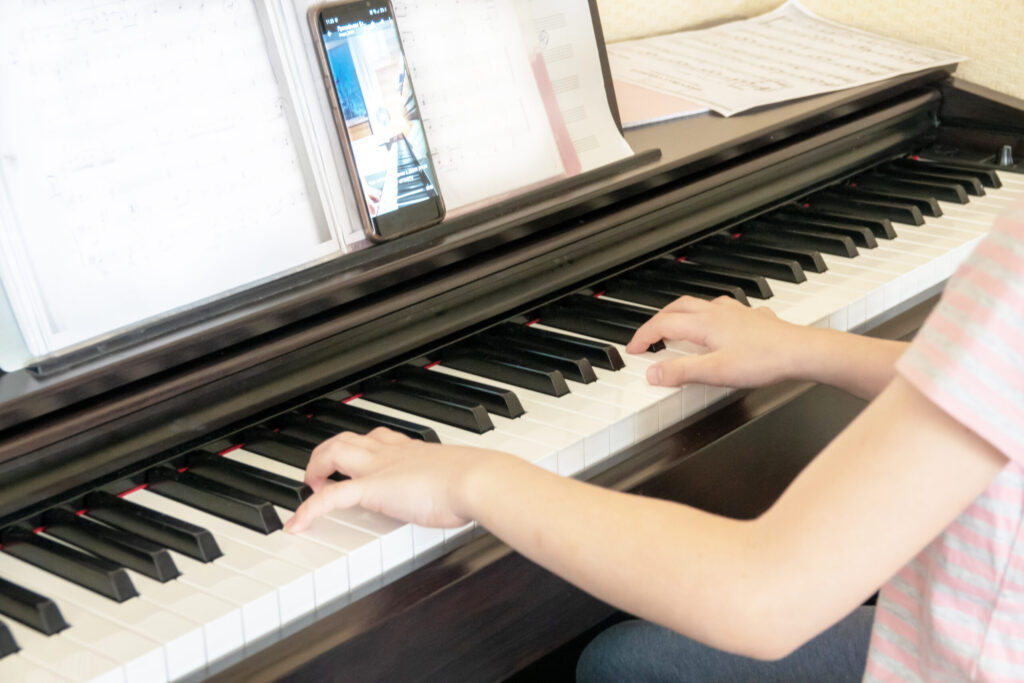 Pretty young musician playing classic digital piano at home during online class at home, social distance during quarantine, self-isolation