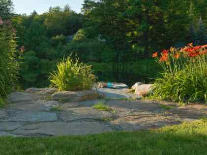 """A flat fieldstone terrace provides a clear entry point to the swimming pond."" p. 199Photo © Susan Teare"