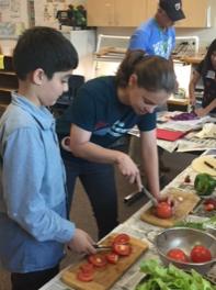 Caitlin Verdu, Arlington 4-H Agent, models safe tomato slicing. EMG Al Schneider oversees cabbage.