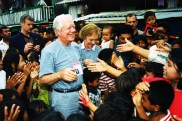 Former U.S. President Jimmy Carter and former First Lady Rosalynn Carter shaking hands with children during the Indonesian elections June 5-9, 1999. The Carter Center has been a pioneer of the field of election observation, monitoring national elections to help deter fraud and reassure voters their votes would count.