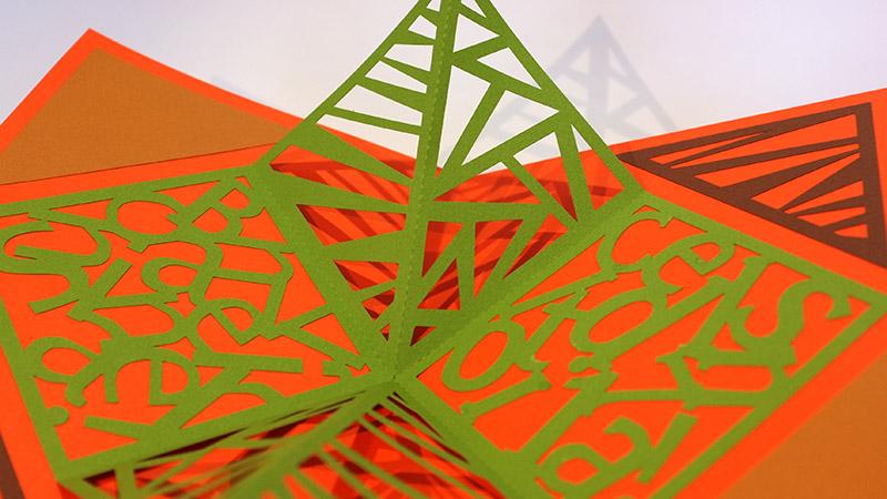 Carré plié d'anniversaire personnalisé avec motifs triangles sur fond orange. Détail des motifs découpés