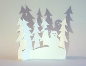 Carte de vœux en papier découpé motif Bonhomme de neige et sapins, vue pliée de face